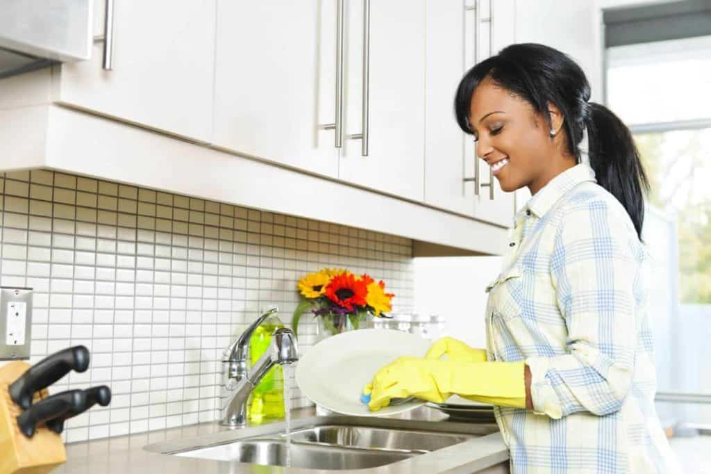 A woman is washing dishes.