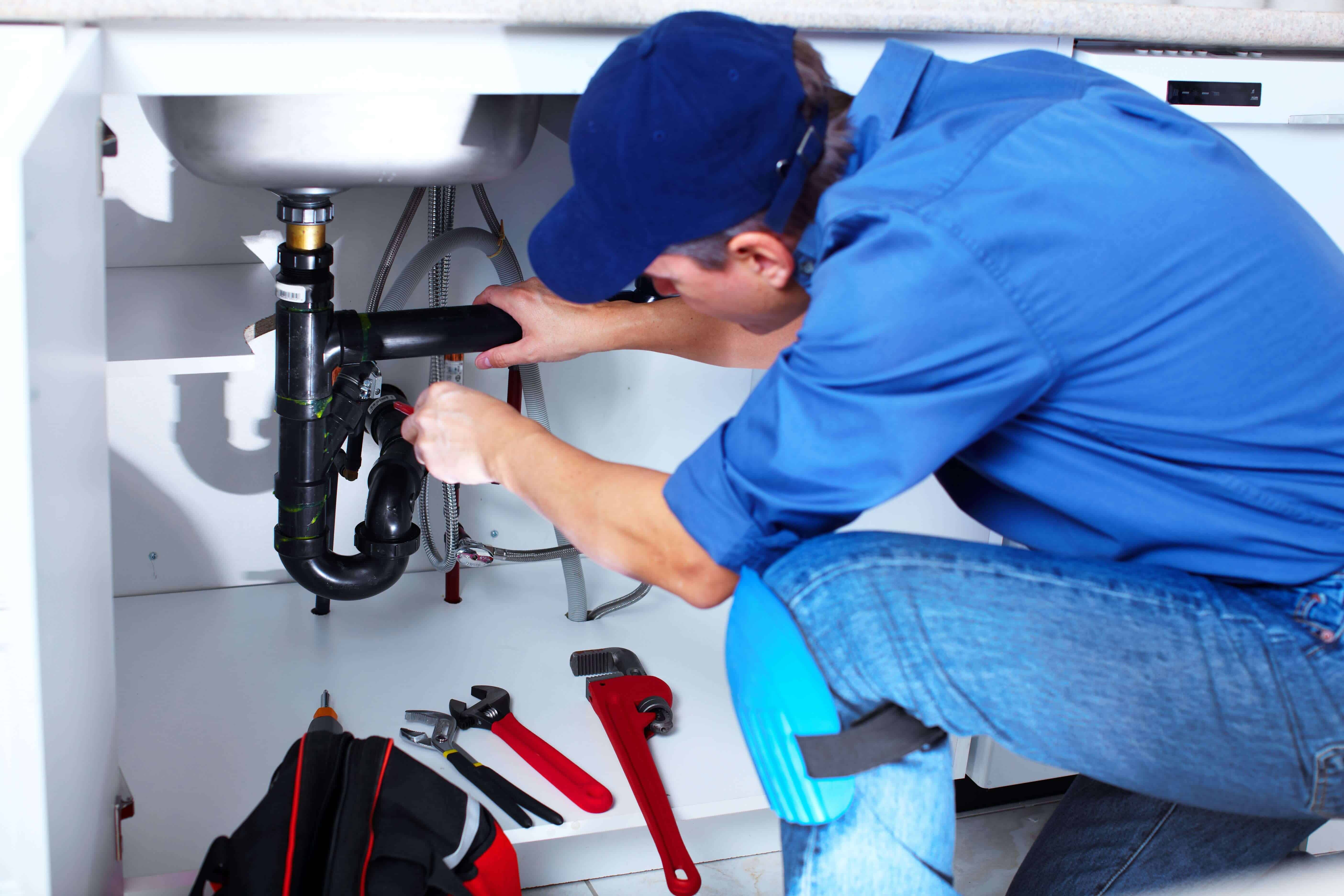 Pictured: A plumber fixing pipes for a sink. We have experts available to fix plumbing issues you might have.
