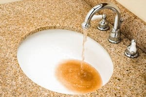 Water with high levels of iron pours out of a faucet into a bathroom sink.